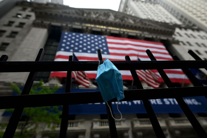 A face mask hangs in front of the New York Stock Exchange in New York on May 26, 2020.