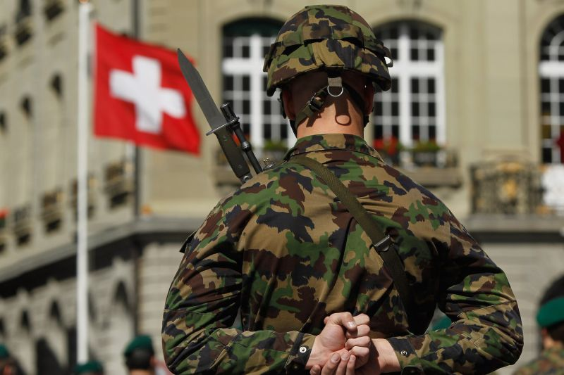 A Swiss soldier stands at attention in front of a Swiss flag in Bern, Switzerland, on Sept. 8, 2010.