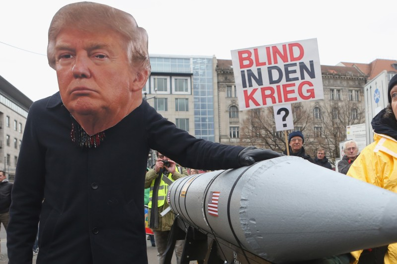 An activist wearing a mask of U.S. President Donald Trump marches with a model of a nuclear rocket during a demonstration against nuclear weapons in Berlin on Nov. 18, 2017.