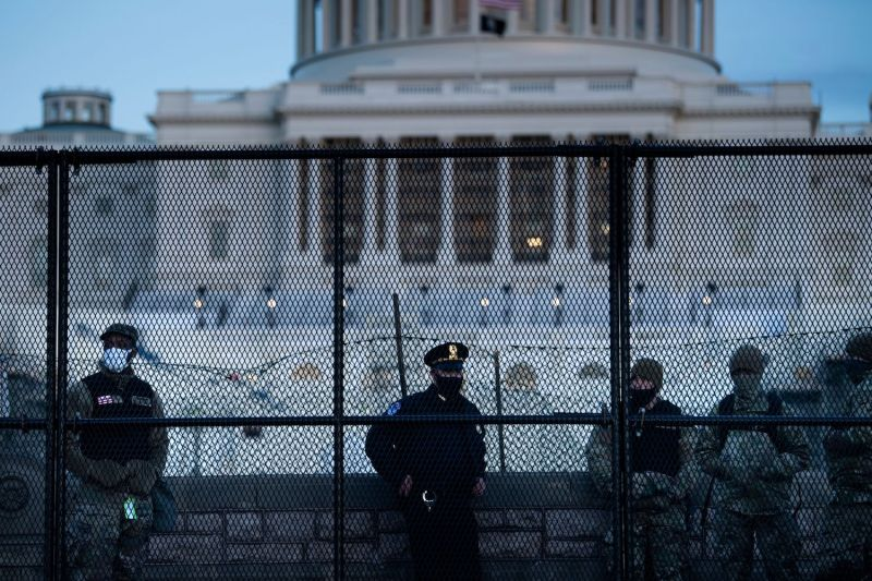 A U.S. Capitol Police officer stands with members of the National Guard behind a fence surrounding Capitol Hill on Jan. 7.