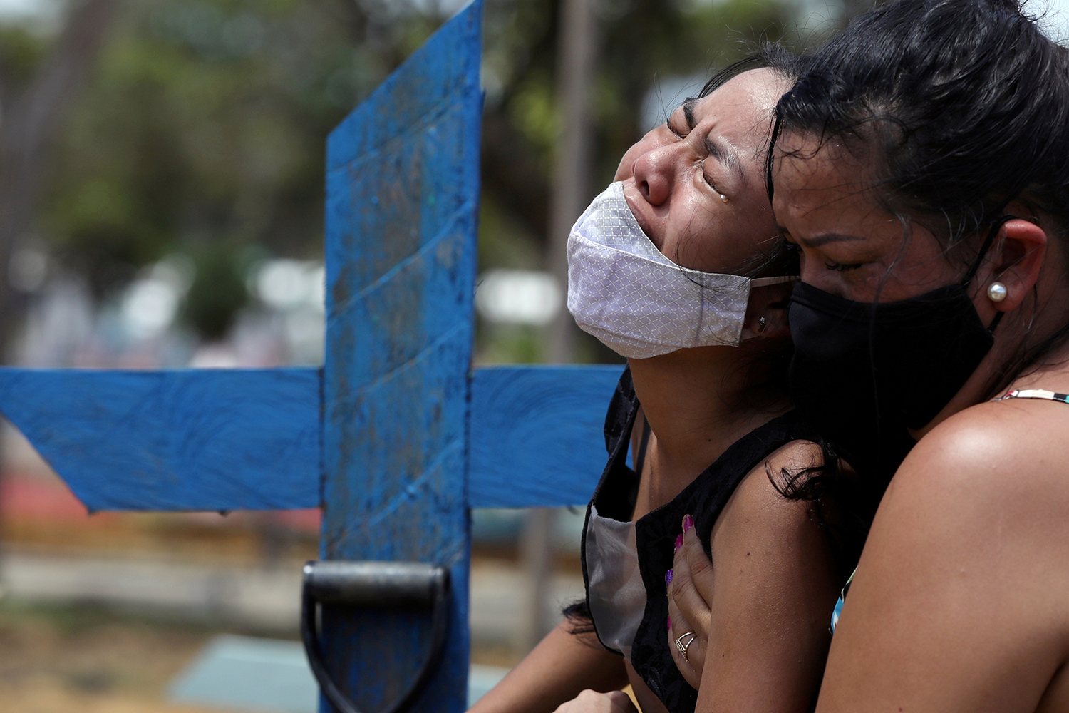 Kelvia Andrea Goncalves, 16, is embraced her aunt Vanderleia dos Reis Brasao during the burial of her mother, who died from COVID-19, at the Parque Taruma cemetery in Manaus, Brazil, on Jan. 17. Bruno Kelly/Reuters