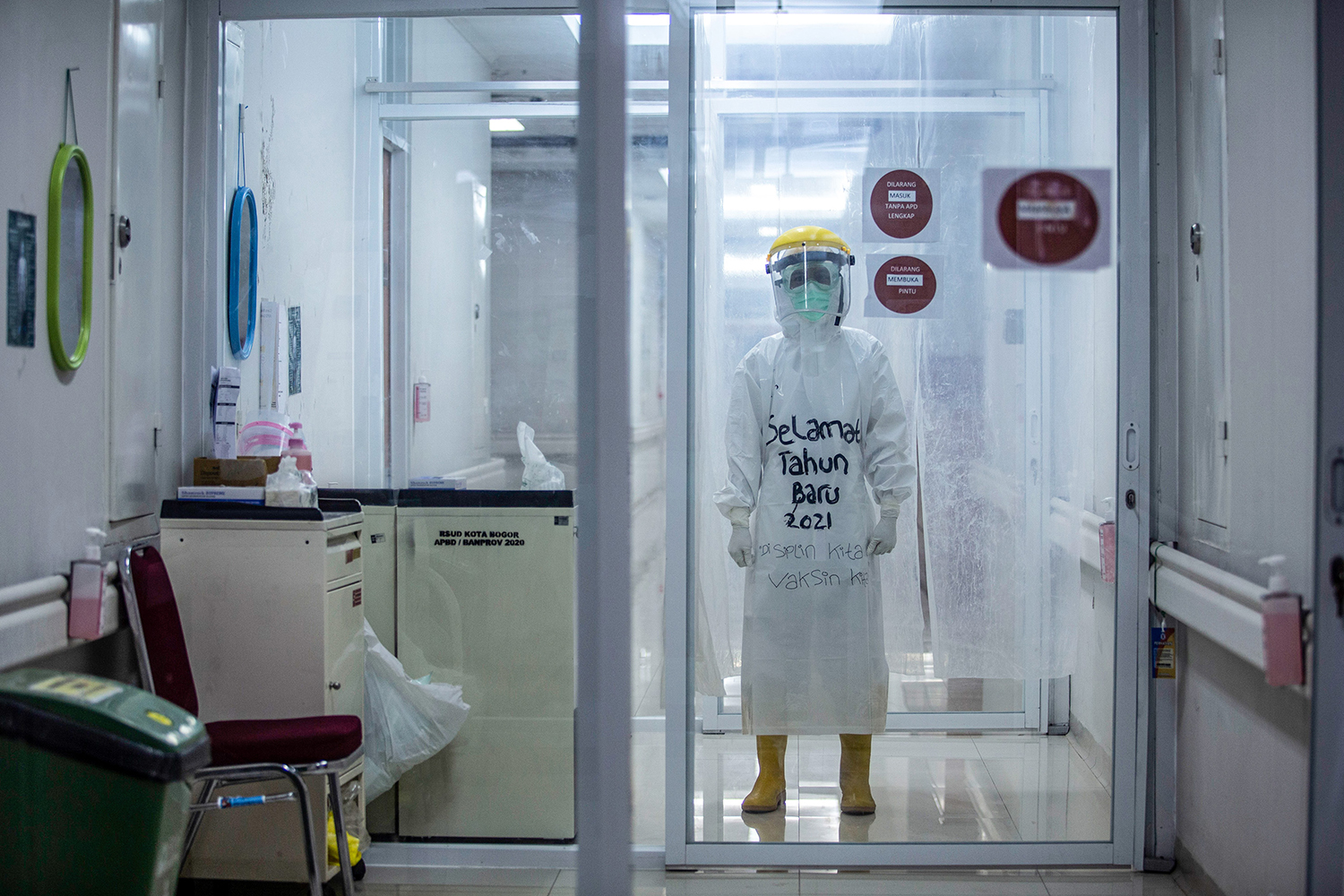 """A medical worker wears personal protective equipment marked with the words """"Happy New Year 2021"""" to encourage COVID-19 patients at the Bogor City Hospital in West Java, Indonesia, on Jan. 1. ADITYA AJI/AFP via Getty Images"""