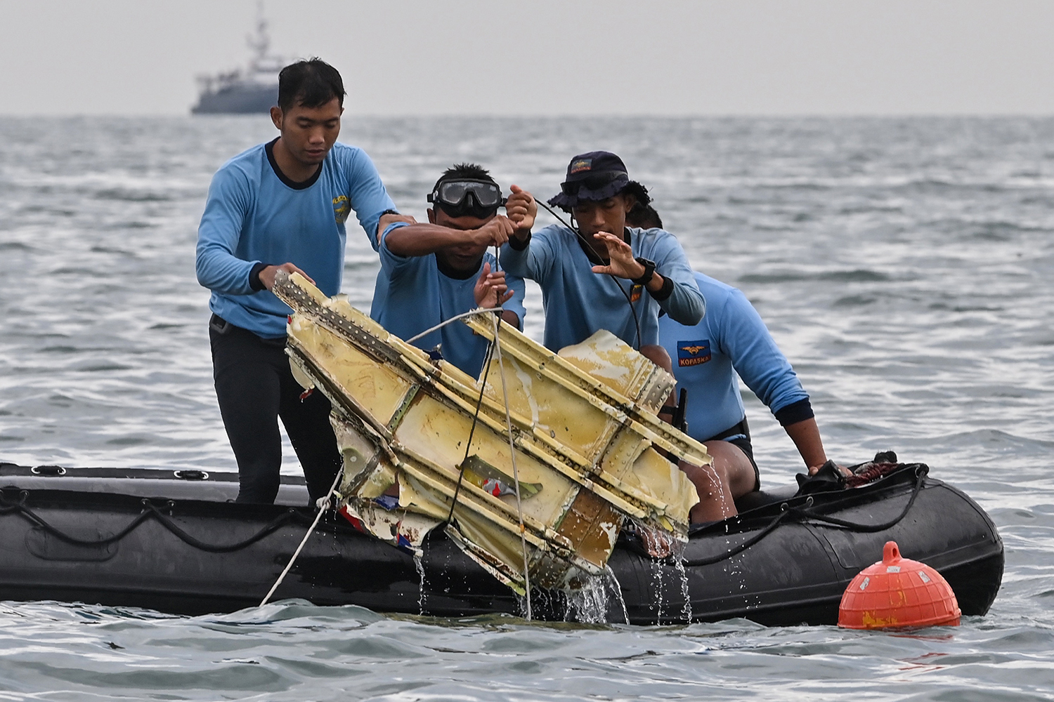 Indonesian Navy divers hold wreckage from Sriwijaya Air Flight 182 during a search-and-rescue operation at sea near Lancang island on Jan. 10. The Boeing 737-500 crashed shortly after takeoff from the Jakarta airport the day before. ADEK BERRY/AFP via Getty Images