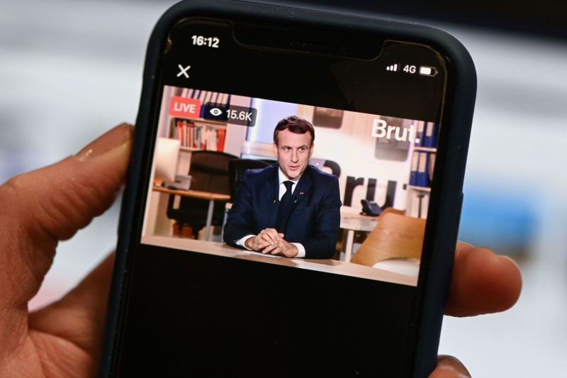 A journalist watches a live stream interview of French President Emmanuel Macron on the digital news platform Brut in Paris on Dec. 4, 2020.