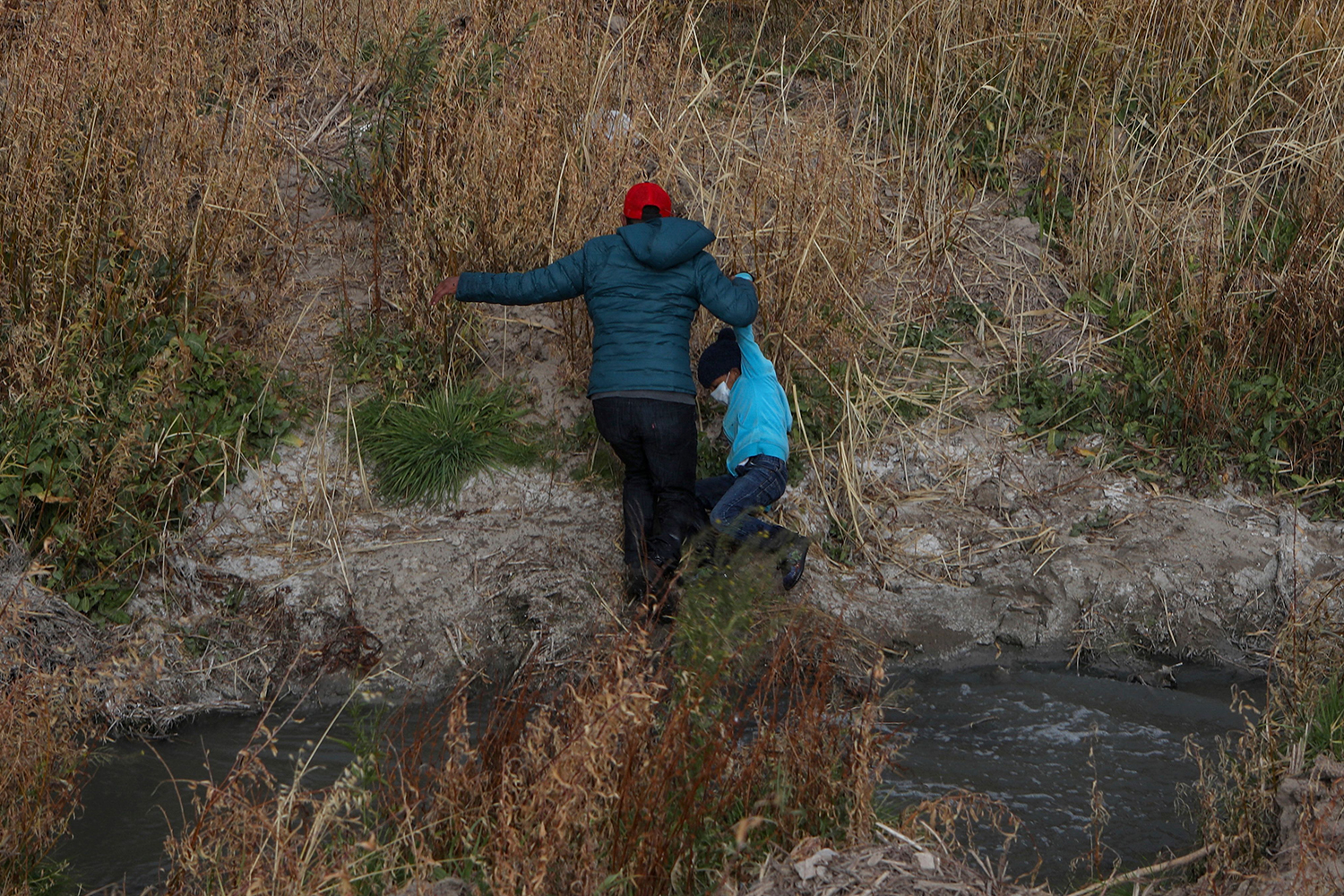 In search of political asylum, a Guatemalan migrant and his son cross the Rio Grande natural border between El Paso, Texas, in the United States and Ciudad Juarez, Chihuahua state, in Mexico on Jan. 26. HERIKA MARTINEZ/AFP via Getty Images