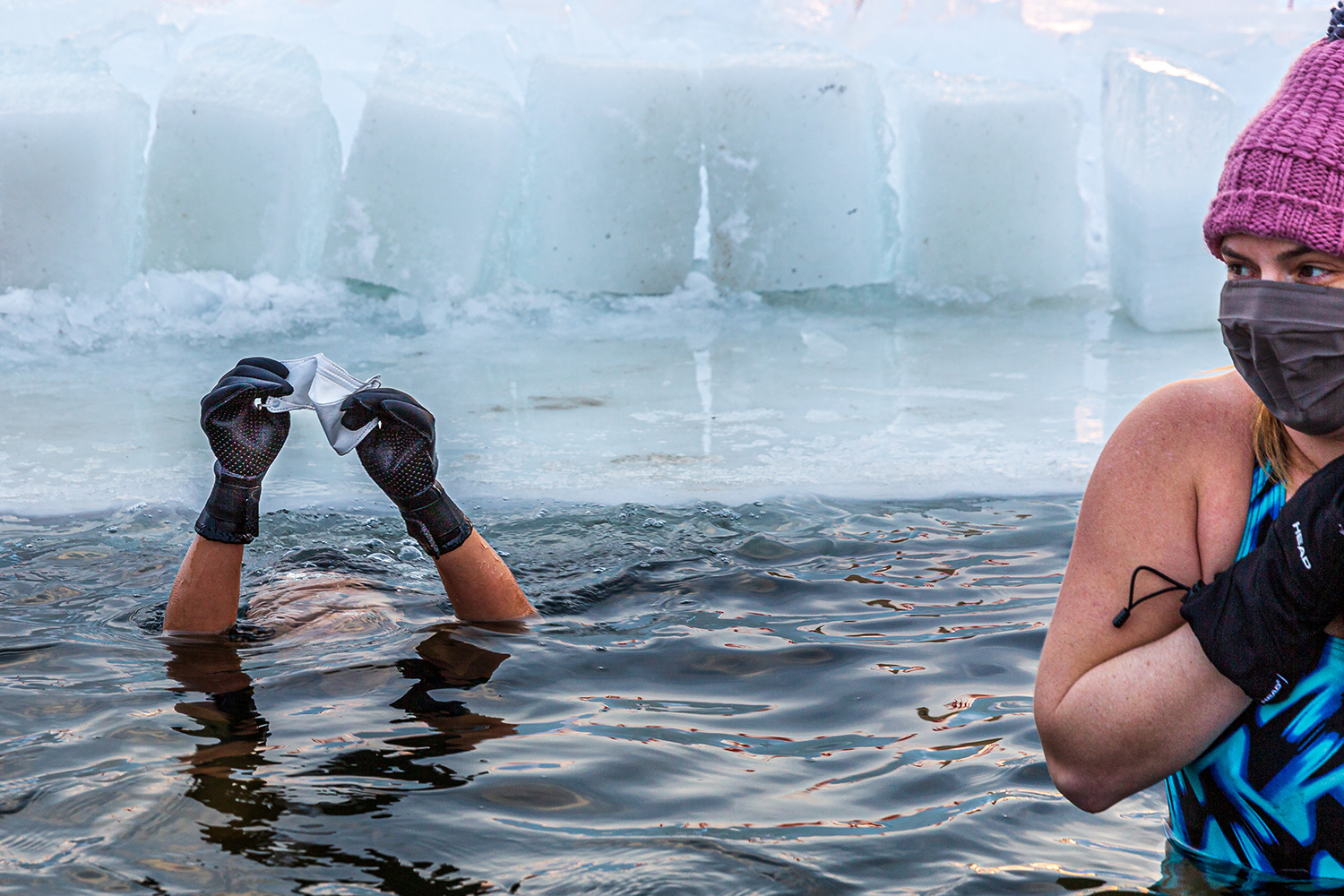 """Members of a """"submergents"""" group take the plunge into 37-degree Fahrenheit water in a pool carved from the ice at Lake Harriet in Minneapolis, Minnesota, on Jan. 30. KEREM YUCEL/AFP via Getty Images"""