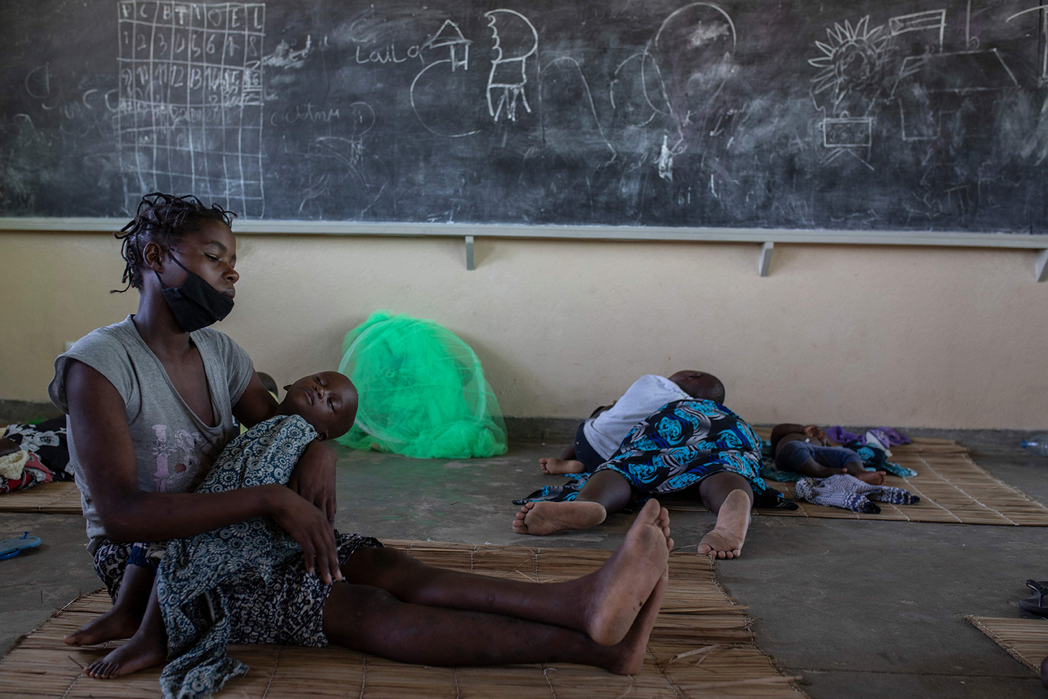 A woman and child take shelter inside a classroom in Beira, Mozambique, on Jan. 27 after being displaced by flooding caused by Cyclone Eloise. ALFREDO ZUNIGA/AFP via Getty Images