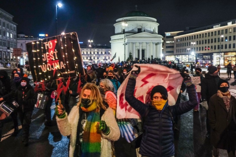 People wearing protective face masks hold banners during a protest against draft laws used to threaten abortion-rights protesters in Warsaw, Poland, on Jan. 20.