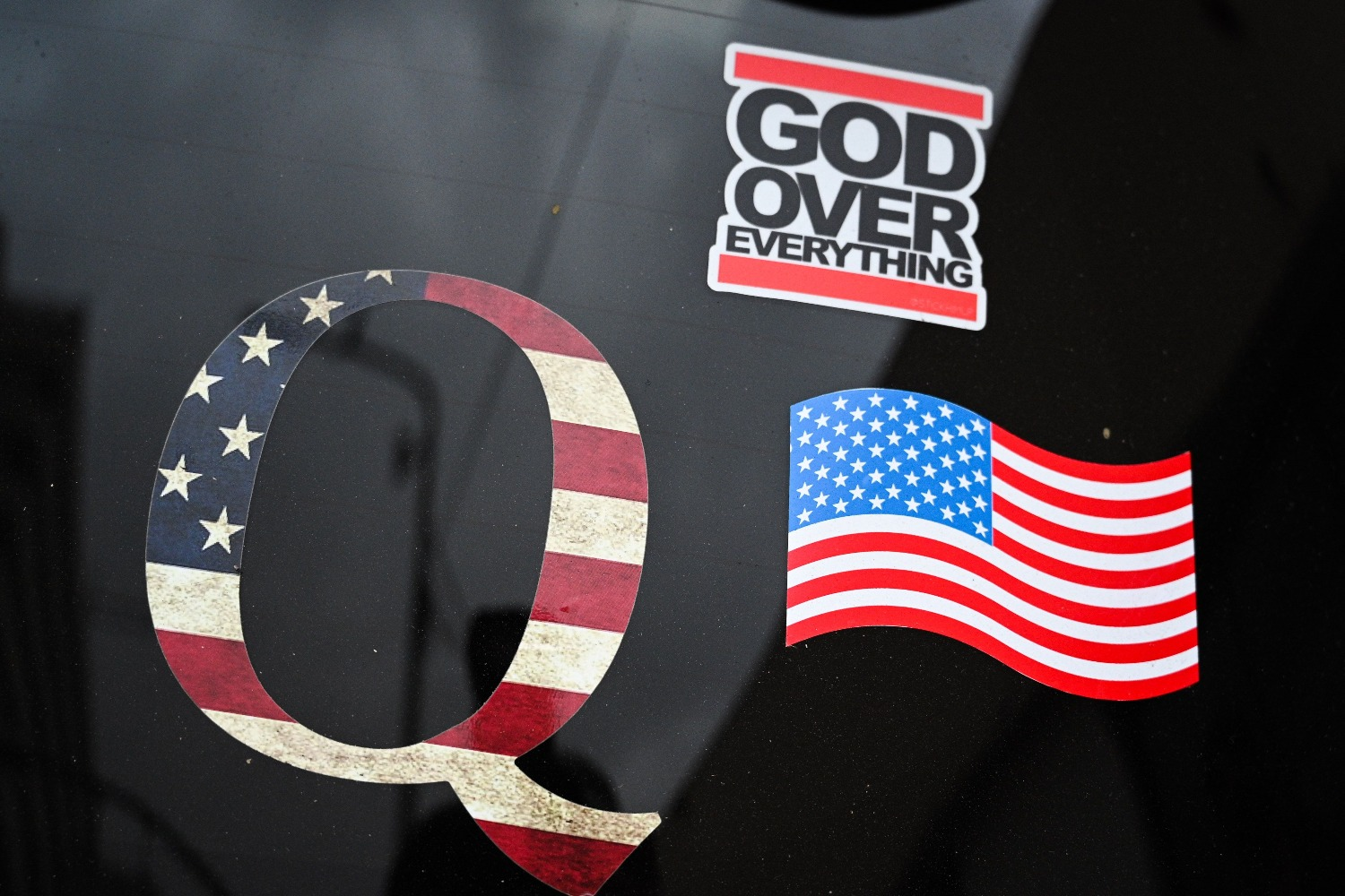 A QAnon sticker is seen on the back of a car