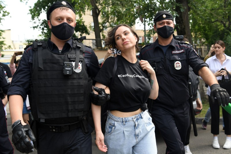 "Police officers detain a woman wearing a T-shirt reading ""Freedom to Safronov"" in Moscow"