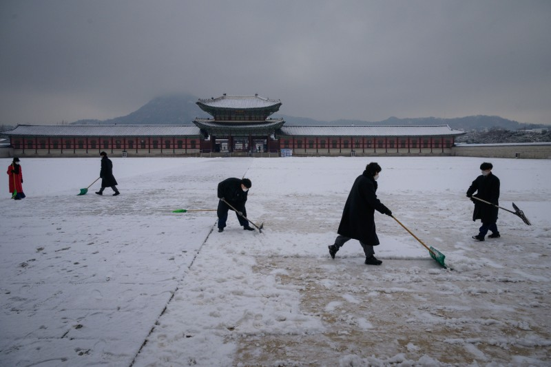 Workers clear snow in Seoul