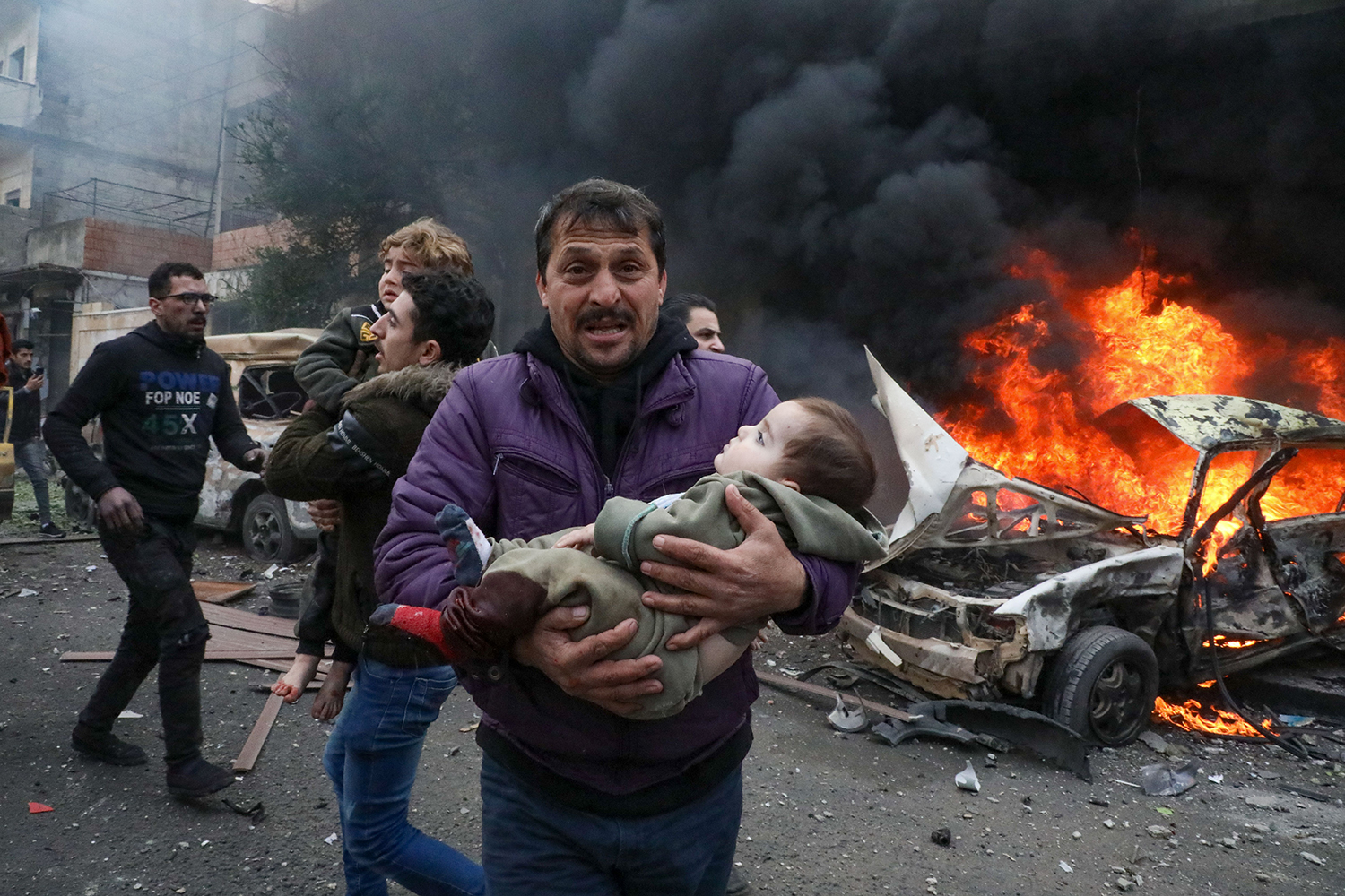 A man carries a young victim at the scene of an explosion in the town of Azaz, in the rebel-controlled northern countryside of Syria's Aleppo province, on Jan. 31. NAYEF AL-ABOUD/AFP via Getty Images