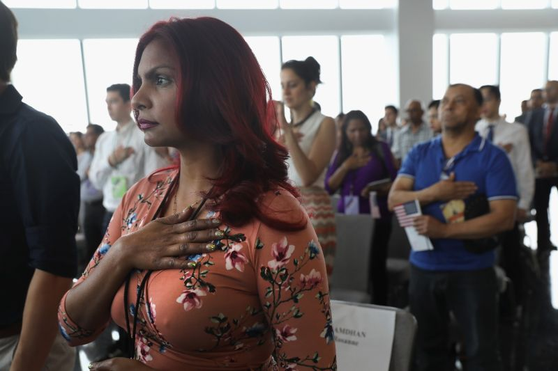 Immigrants listen to the National Anthem