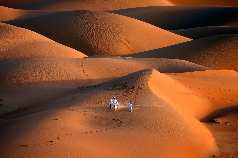 Emirati youths run across a sand dune in the Liwa desert in United Arab Emirates on Jan. 9. KARIM SAHIB/AFP via Getty Images