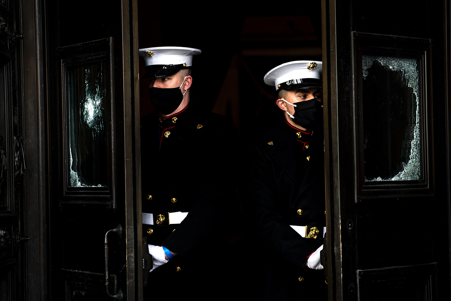 Shattered glass windows on the east front steps of the U.S. Capitol are a reminder of the insurrection that occurred two weeks prior as the Honor Guard runs through a rehearsal for the presidential inauguration in Washington on Jan. 18. Melina Mara-Pool/Getty Images