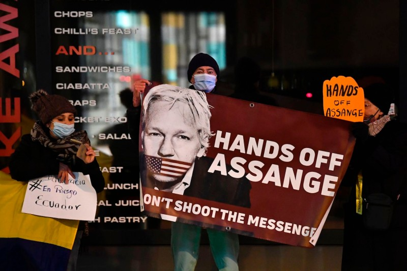 Protesters hold a sign to support WikiLeaks founder Julian Assange in front of the EU British Embassy in Brussels on December 07, 2020.