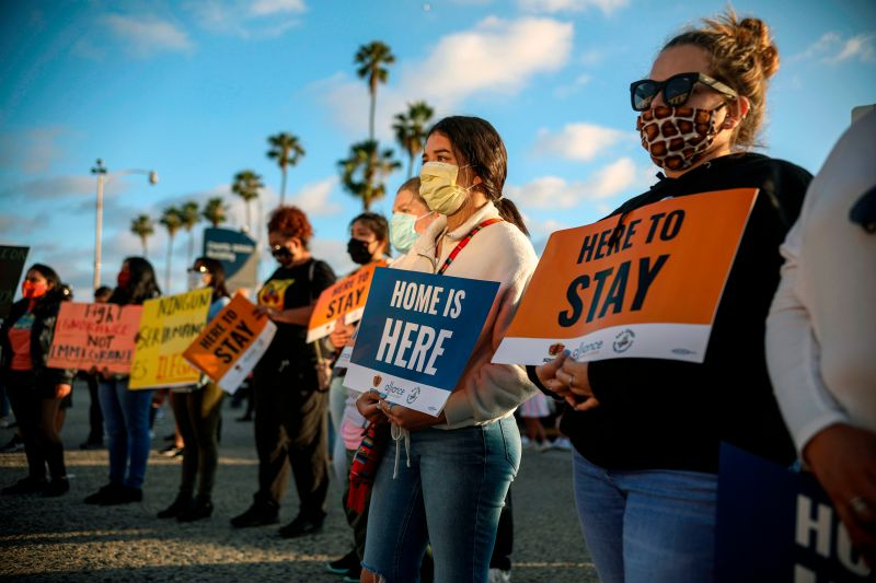 People hold signs during a rally in support of the Deferred Action for Childhood Arrivals program in San Diego on June 18, 2020.