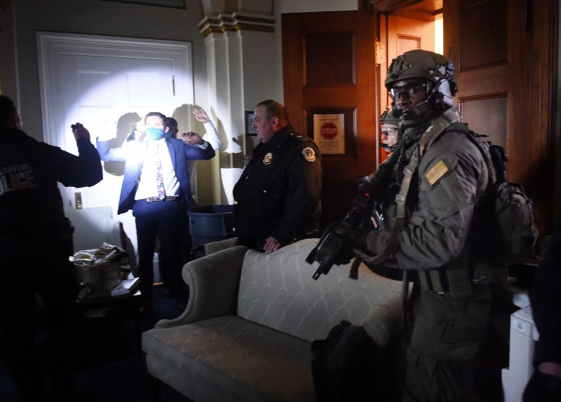 Congressional staffers hold up their hands while Capitol Police SWAT teams secure the floor in Washington, DC on January 6, 2021.