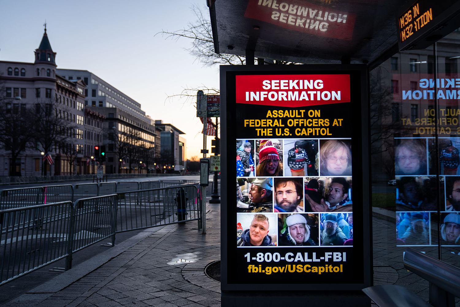 A bus stop sign, seen from Pennsylvania Avenue in Washington on Jan. 16, seeks information about rioters who breached the Capitol building.
