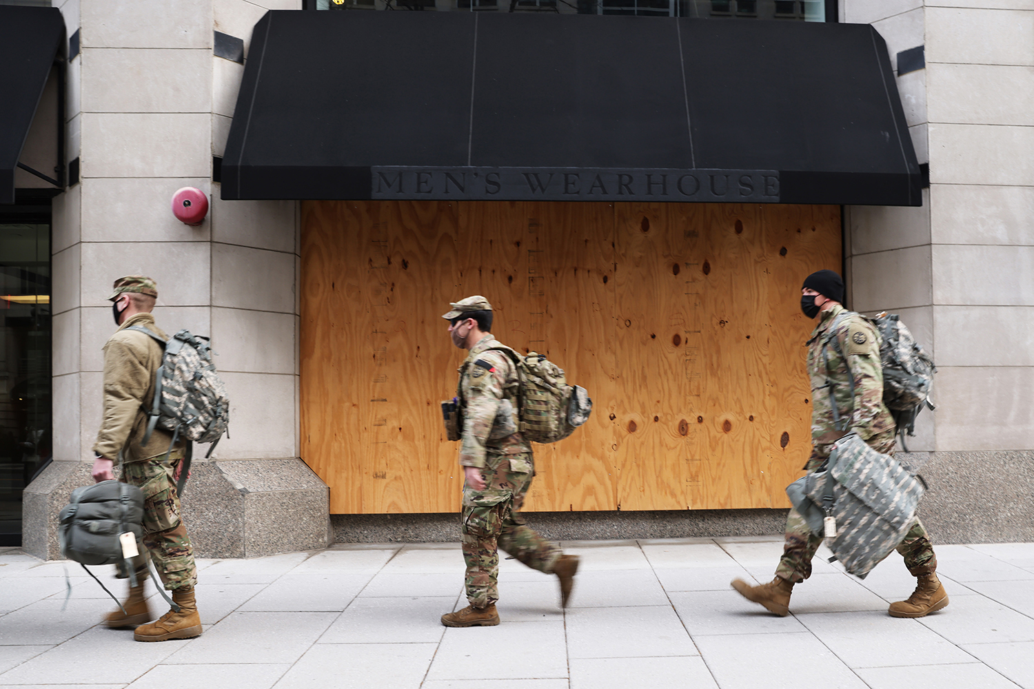 Members of the National Guard walk past a boarded-up store in downtown Washington on Jan. 16.