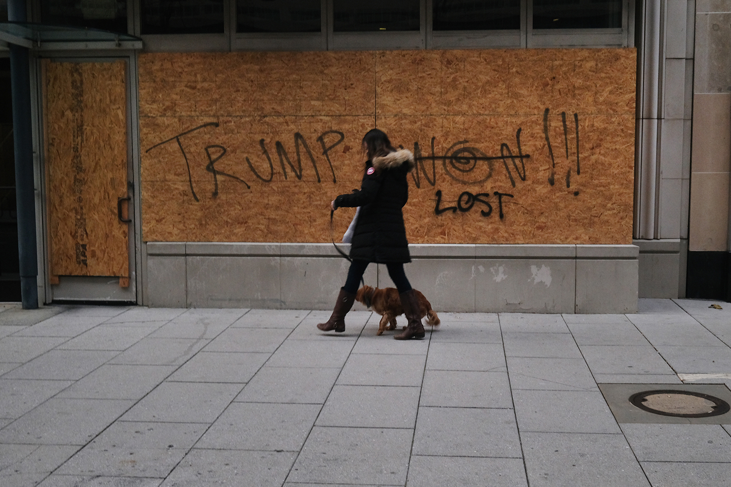 A person walks a dog past a boarded-up business in Washington on Jan. 16.