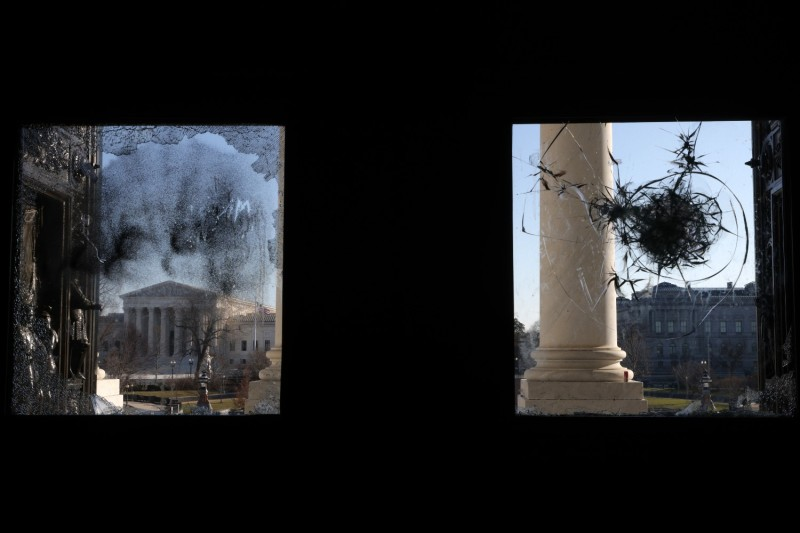 The U.S. Supreme Court is seen through a damaged entrance of the U.S. Capitol in Washington on Jan. 7.
