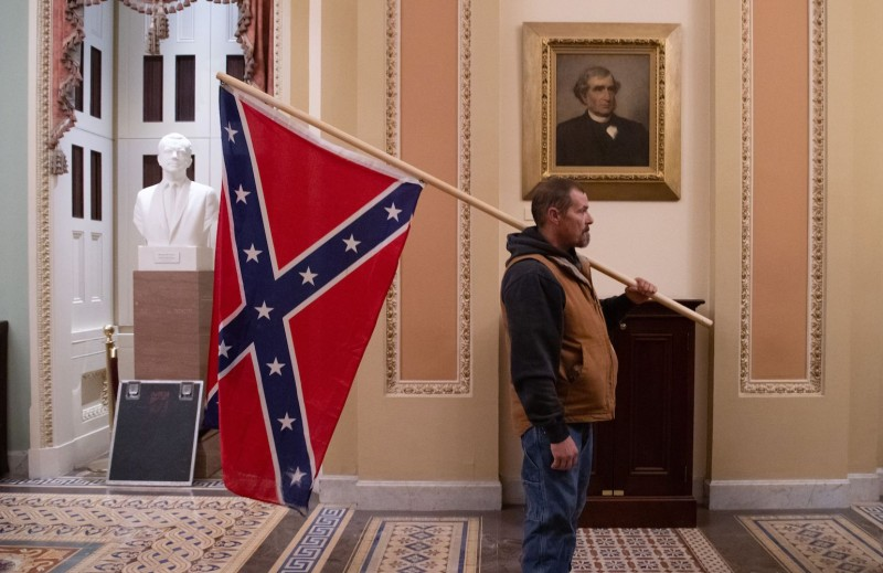 A supporter of U.S. President Donald Trump holds a Confederate flag outside the Senate Chamber after breaching the U.S. Capitol on Jan. 6.