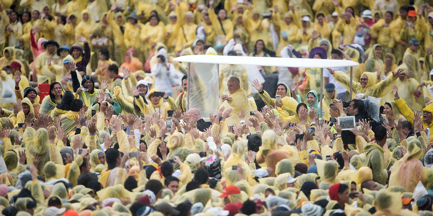 Pope Francis wears a plastic poncho as he waves to well wishers after a Mass in Tacloban on Jan. 17, 2015. The pope spent an emotional day in the Philippines with surviors of a catastrophic syper typhoon that claimed thousands of lives, highlighting his concern over climate change.