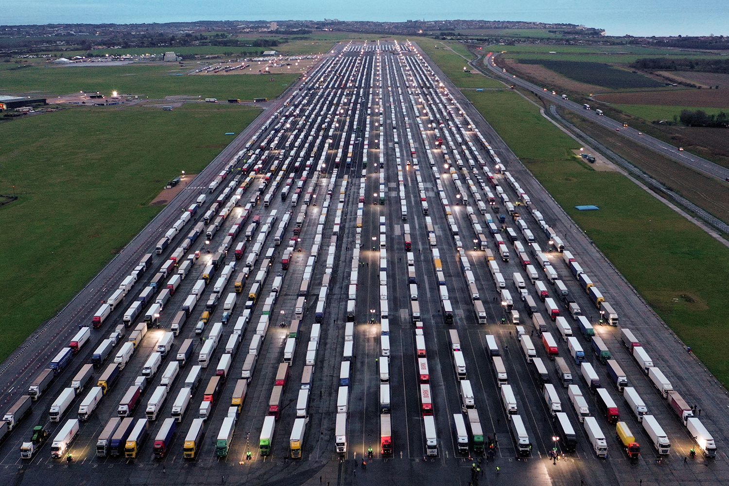An aerial view shows lines of freight trucks parked on the tarmac at Manston Airport in England on Dec. 22, 2020, after France closed its borders to freight arriving from the United Kingdom due to the rapid spread of a new coronavirus strain. WILLIAM EDWARDS/AFP via Getty Images