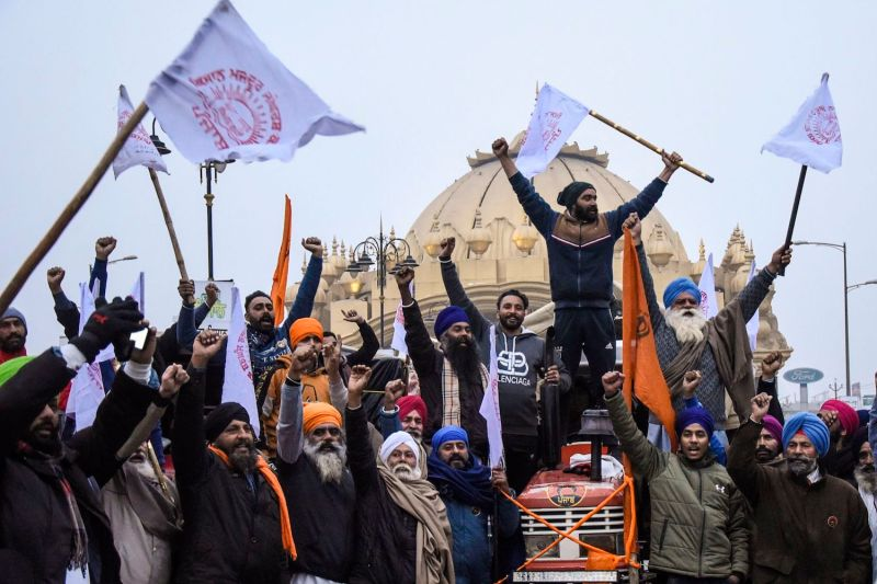 Farmers shout slogans as they depart for Delhi to participate in a continued demonstrations against the central government's recent agricultural reforms in Amritsar on Jan. 12.