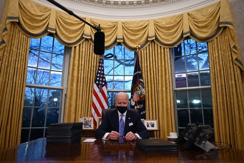 U.S. President Joe Biden holds a pen as he prepares to sign a series of orders in the Oval Office of the White House in Washington on Jan. 20.