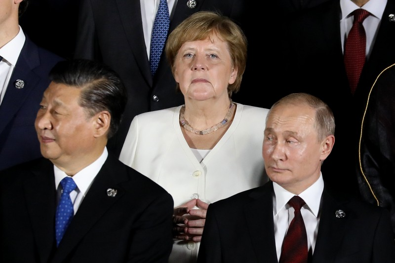 German Chancellor Angela Merkel stands behind Chinese President Xi Jinping and Russian President Vladimir Putin during the G20 summit in Osaka on June 28, 2019.