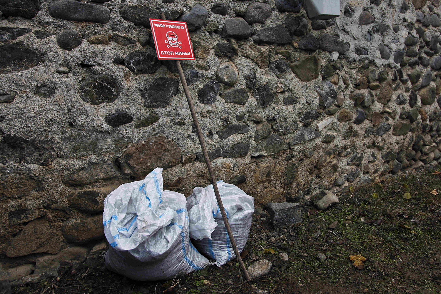 "A skull-and-crossbones sign saying ""Stop Mines"" is placed next to sandbags encasing an unexploded cannon round in the the village of Aygestan on Dec. 3, 2020."