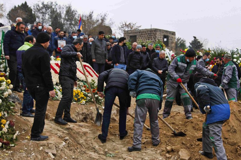 Men dig a grave in front of mourners at Yerablur Military Memorial Cemetery near Yerevan, Armenia.