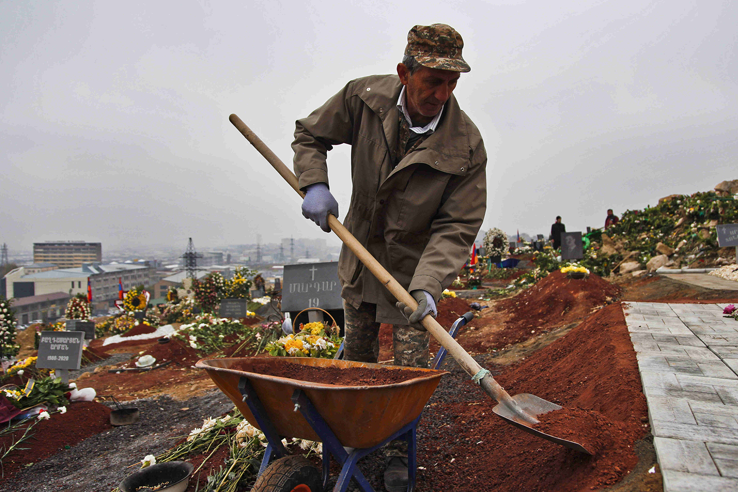 A gravedigger shovels earth around a new memorial at Yerablur Military Memorial Cemetery on Nov. 30, 2020.