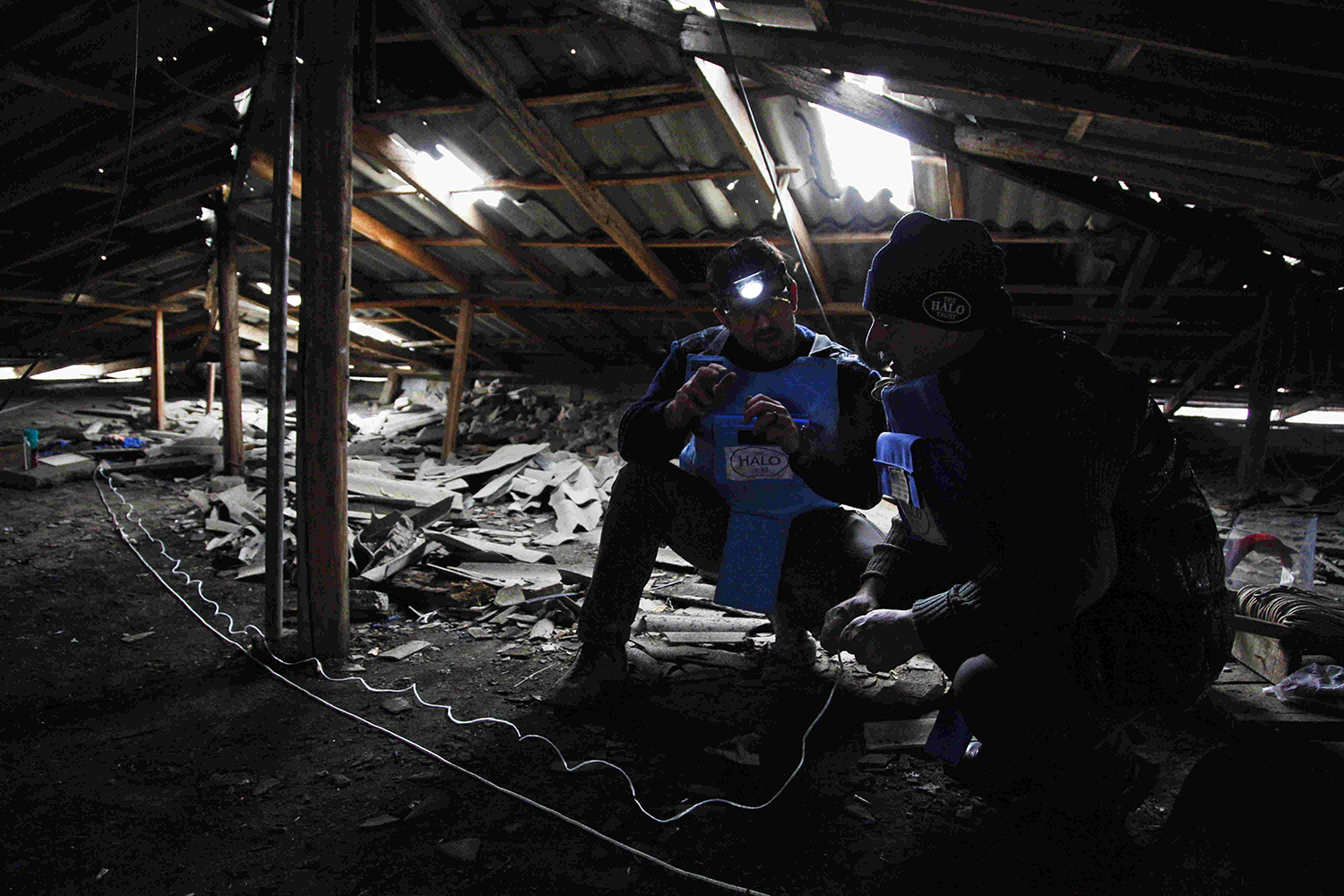 Two specialists from the HALO Trust humanitarian demining group prepare to remove an unexploded cluster bomb from the roof of an apartment block in Stepanakert, Nagorno-Karabakh, on Dec. 3, 2020.