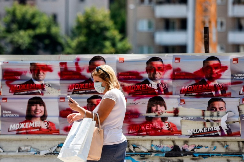 A woman walks in front of electoral posters of the ruling Social Democratic Union of Macedonia party in Skopje, North Macedonia, on July 14, 2020.