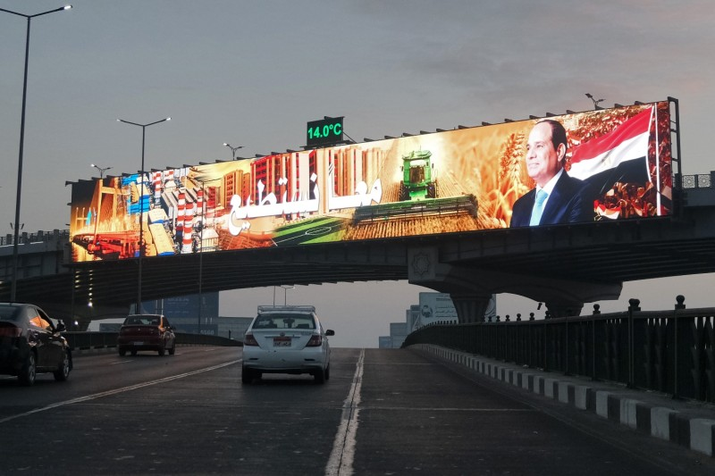 """Cars pass beneath an electronic billboard depicting Egyptian President Abdel Fattah al-Sisi and the phrase """"Together we can"""" in Cairo on Jan. 15."""