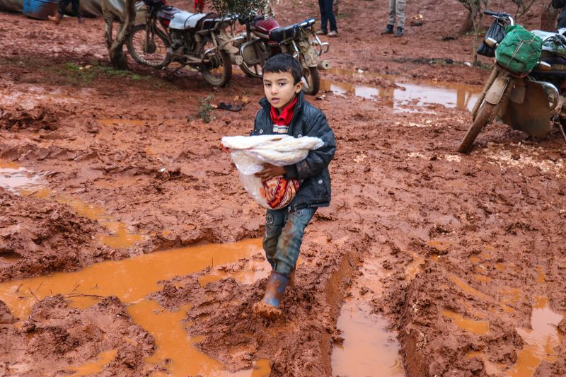 A Syrian child carries food through a muddy camp
