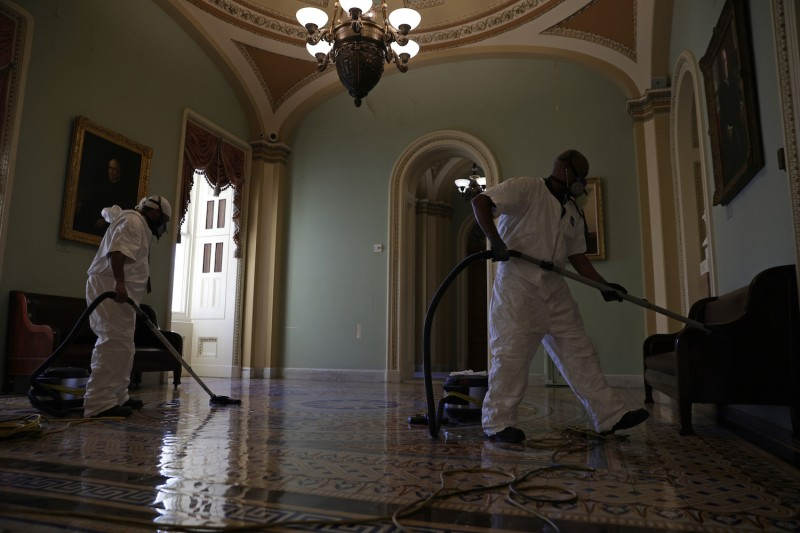 A cleaning crew vacuums the floor of a hallway at the U.S. Capitol January 7, 2021 in Washington, DC.