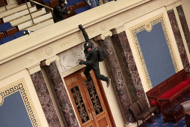 A protester is seen hanging from the balcony in the Senate chamber in Washington on Jan. 6. as pro-Trump protesters have entered the U.S. Capitol building.