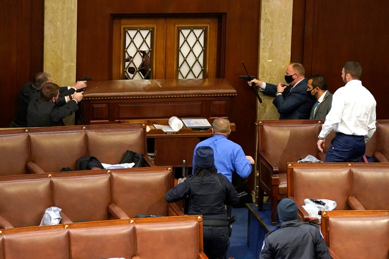 U.S. Capitol police officers point their guns at a door broken by pro-Trump extremists during a joint session of Congress in Washington, DC, on Jan. 6.