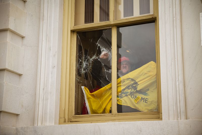 A member of a pro-Trump mob shatters a window with his fist from inside the Capitol building in Washington after breaking into it on Jan. 6.