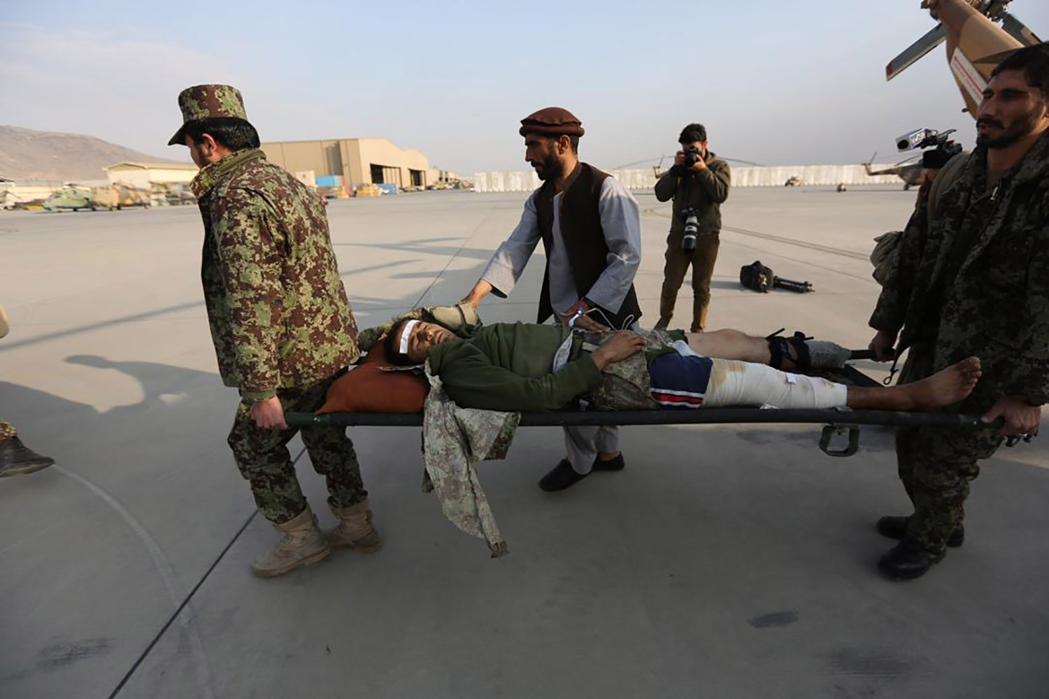 Jalali, background, photographs the evacuation of soldiers wounded in the battlefield in Kabul in an archival photo.