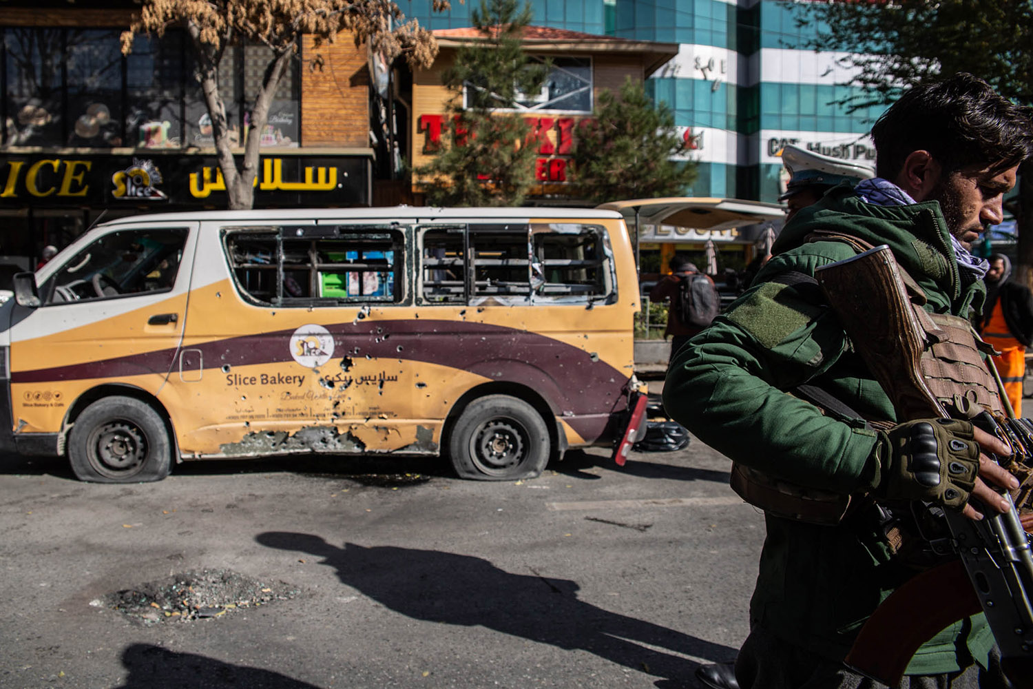Security forces stand outside Slice Bakery in Share-Naw in Kabul, Afghanistan, on Nov. 21, 2020, where one of 23 rockets hit, damaging a delivery van and injuring several people. This attack prompted Jawad Jalali to relocate his family to Turkey.