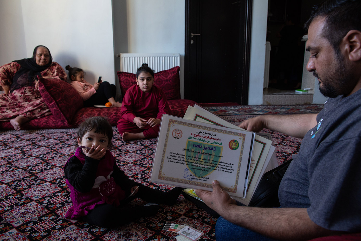 Massoud Ahmad Niaz sits at his home with his family on Jan. 28.. Massoud, who worked for U.S. forces as a mechanic for many years says he doesn't feel safe anymore and has applied for a visa to Pakistan.