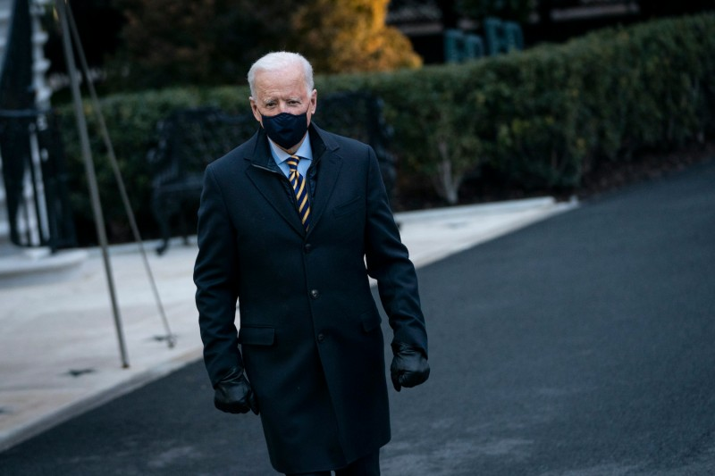 President Joe Biden walks toward reporters at the White House.