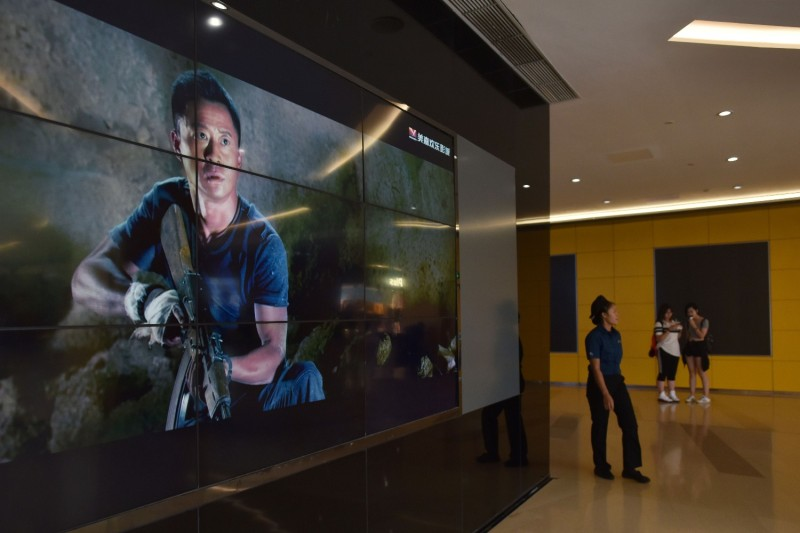 "A woman walks past a video screen showing scenes from the movie ""Wolf Warrior 2"" outside a theater in Beijing, on Aug. 21, 2017."