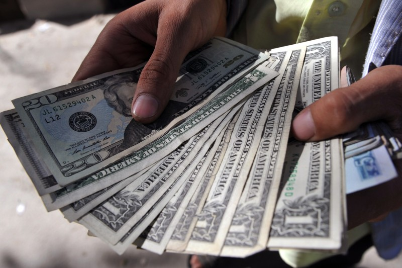 An Afghan moneychanger counts U.S. dollar notes