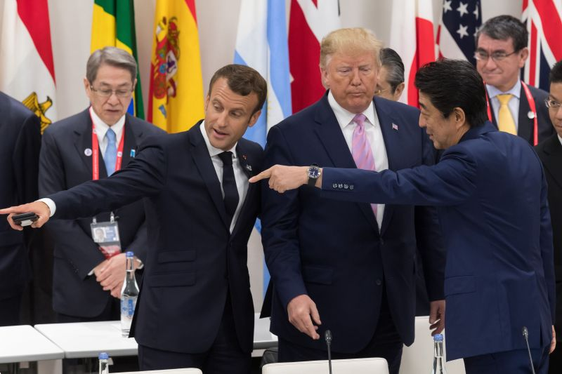France's President Emmanuel Macron and Japan's Prime Minister Shinzo Abe gesture to US President Donald Trump as they attend a meeting on the digital economy at the G-20 Summit in Osaka on June 28, 2019.